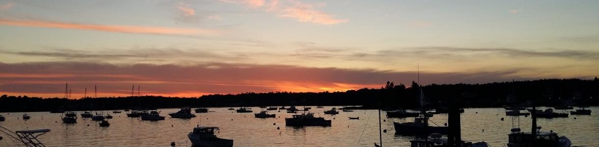Image of sun setting over boats in Boothbay Harbor, Maine.