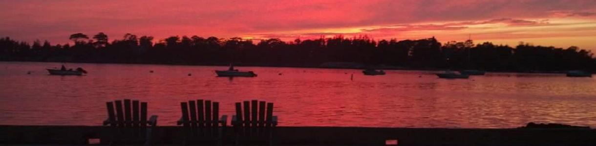 Image of setting sun with silhouette of Adirondack chairs.